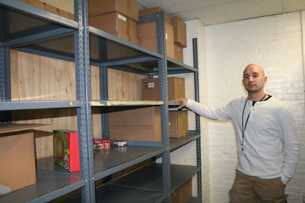 FOOD SHORTAGE: Scott Dodd, the administrative aide at Comprehensive Community Action Program in Cranston, shows the thinning collection of food on the shelves of the CCAP food pantry, which serves 500 to 600 families.