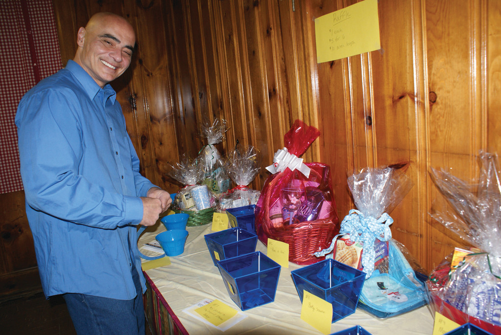 "TAKING A CHANCE: John Cece of Cranston places his raffle tickets in the raffle cups during the Oaklawn Grange's Pasta Dinner, which raised funds for their upcoming Tree Lighting Ceremony on Dec. 14. Cece stated he was most thankful that ""I have been given the opportunity to be helpful in some people's lives."""