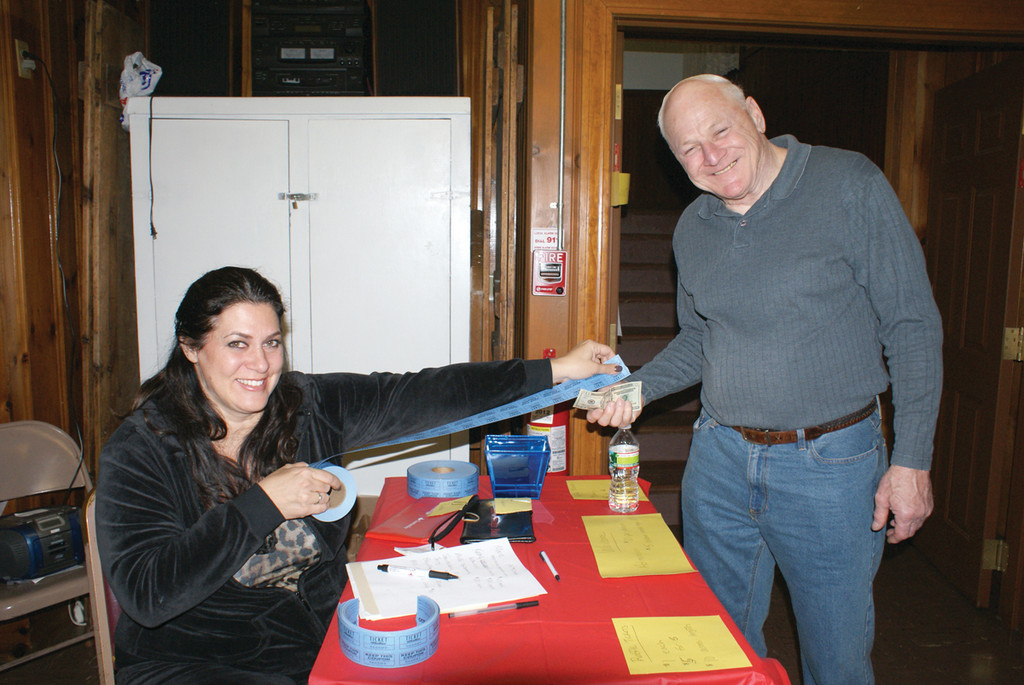 ARM'S LENGTH: Selling an arm's length of raffle tickets to Grange Master Gerald Bloomfield is Maria Manzi, the Grange secretary. Bloomfield was grateful for his health and Manzi was grateful for her family and friends this Thanksgiving week.