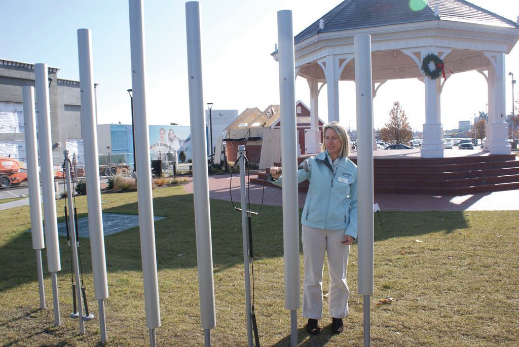 SLEIGH BELLS RING: Janice Pascone, marketing director for Garden City, tests out the Contrabass Chimes that have been added to the gazebo area.