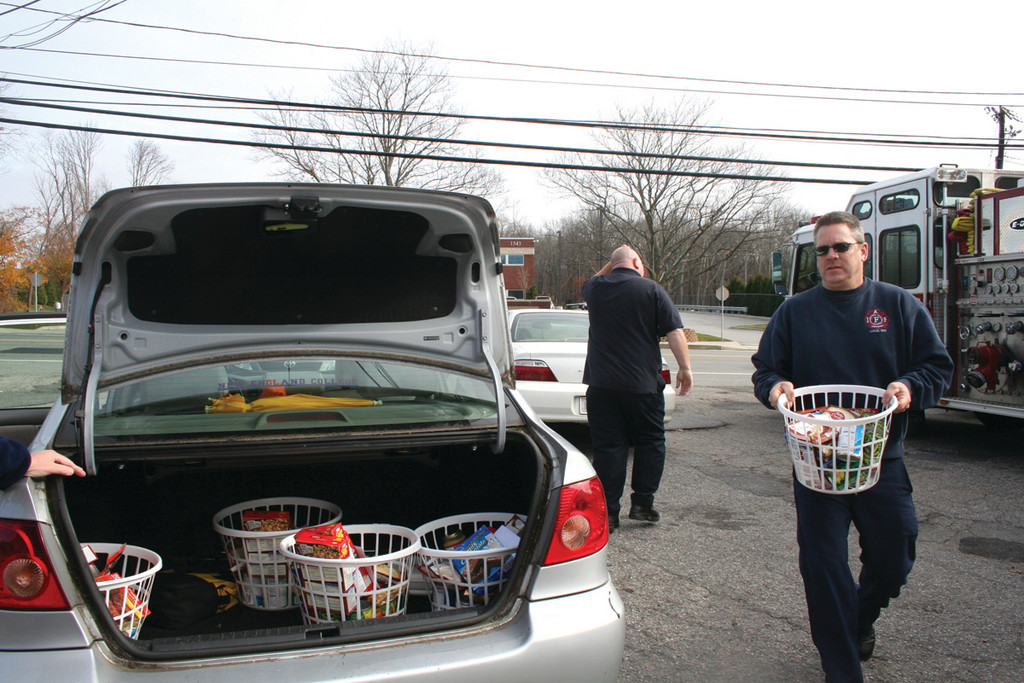 Private Stephen Veresko from Engine 3 packs up the car for a representative from the district, who brought the baskets to the school for distribution.