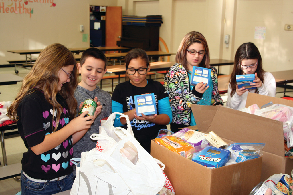 Delaney LaRose, Joshua Brien, Dyemin Ratchford, Angelina Emerson and Stephanie McCoy check out some of the donated food items for this year's Thanksgiving food drive.