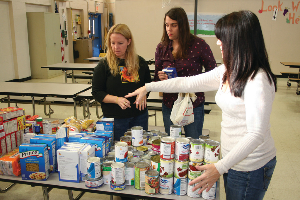Parent volunteers Kristen Brien, Bethany Littlefield and Marga Spence help the students fill the bags with donated foods.