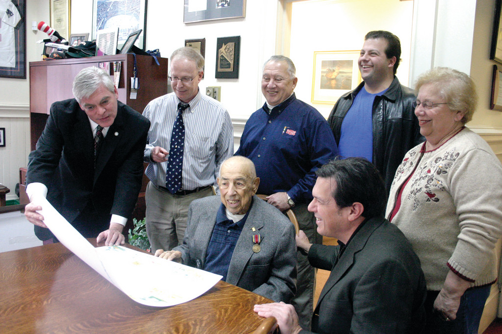 APPRECIATIVE: Avedisian (left) and Galasso (bottom right) take a look at an early draft of the lithograph, along with (from left) Arnold Bromberg of Benny's, Barry Newman of Warwick Ice Cream, Peter Xiarhos of Sam's New York System, and Carol Pratt of Carol's Country Corner. Sitting front and center is Frank Amalfetano, who opened Jenny's Ice Cream in 1949.