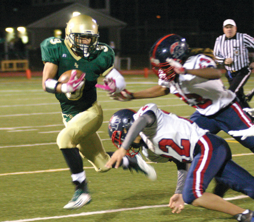 FULL SPEED: Hendricken's Jarrid Witherspoon avoids two Toll Gate tacklers in the Thanksgiving eve game. The Hawks won 33-0.