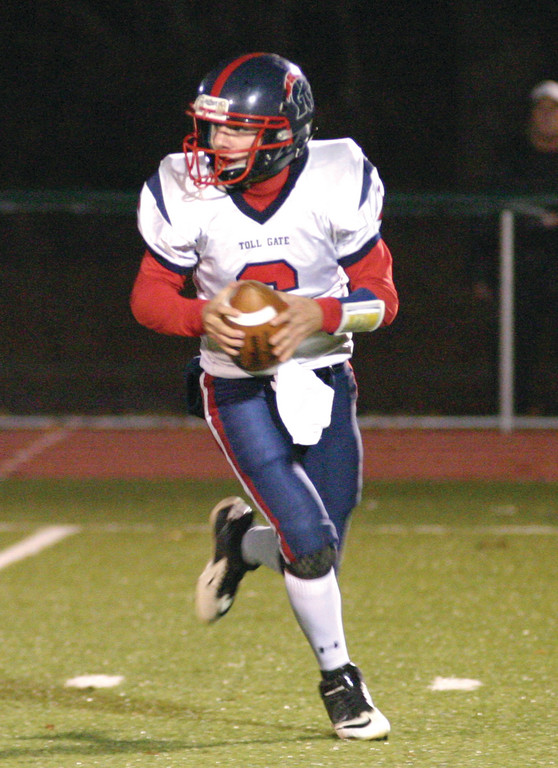 ROLLING: Toll Gate quarterback Dave Babcock rolls out during Wednesday night's game.