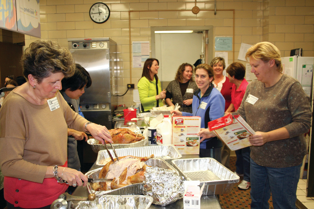 IT TAKES A VILLAGE: The annual first and second grade Thanksgiving dinner would not be possible without the help of all the parent volunteers who spend hours cooking the meal for the students.