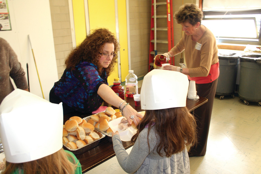 NEW FACE, FAMILIAR TRADITION: Principal Tonianne Napolitano helps out in the buffet line for her first Thanksgiving dinner at Garden City Elementary School.