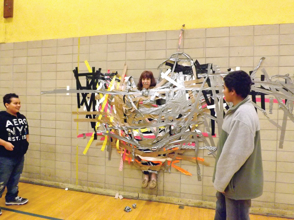 IT ACTUALLY WORKED: Seventh grade math teacher Joanne Spaziano is stuck to a wall with duct tape by her students. It was a reward for bringing in cans for the school's holiday food drive.