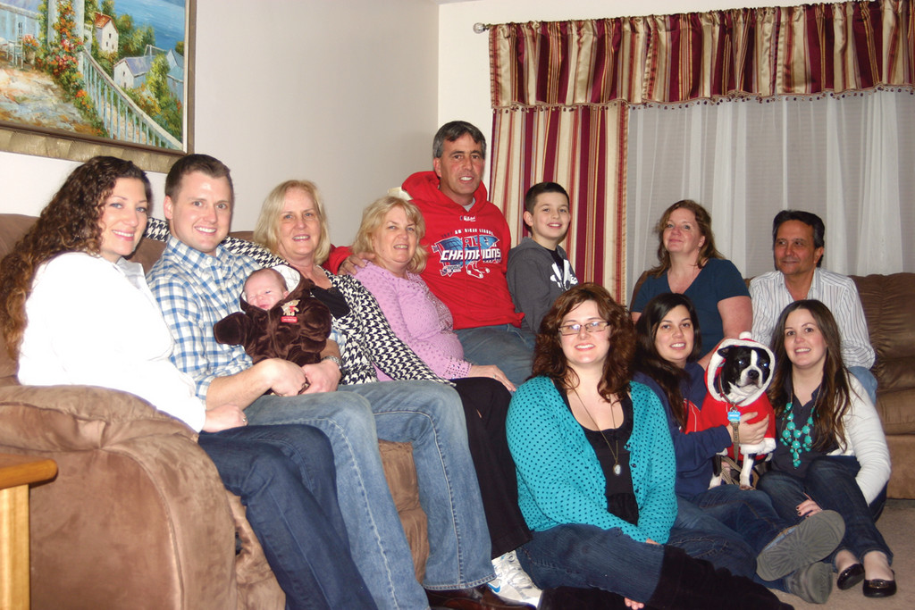 FAMILY TRADITION: At least 50 people gathered in front of the Picozzi home at 8:30 Thanksgiving night, which he does each year. Picozzi (center) is surrounded by his family, including his wife, Kim, who sits to his left, and his daughters, Stephanie and Jackie, who hold Buster, one of their dogs.