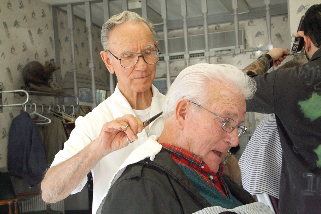 JUST A TRIM: Henry Lozier trims the hair of Paul Maggiacomo of Louie's Barber Shop, who hired him 51 years ago.