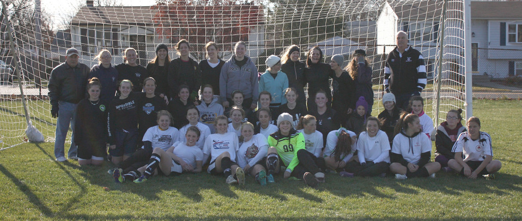 Pilgrim alumni and members of the current soccer team pose for a photo on Saturday at the Giving Game.