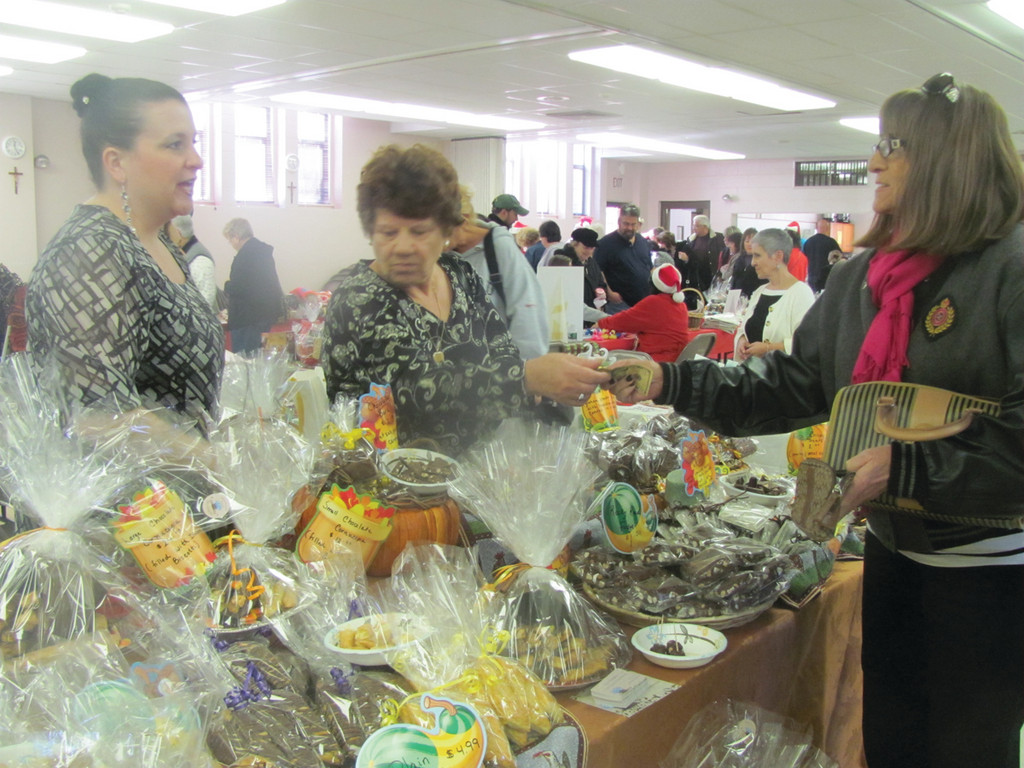 Di�s Delights, a display of sweet treats that included chocolate, fudge and more, was a popular booth at the Holiday Bazaar. Pictured here, Rita Paris and Diana Sorafine help a customer.