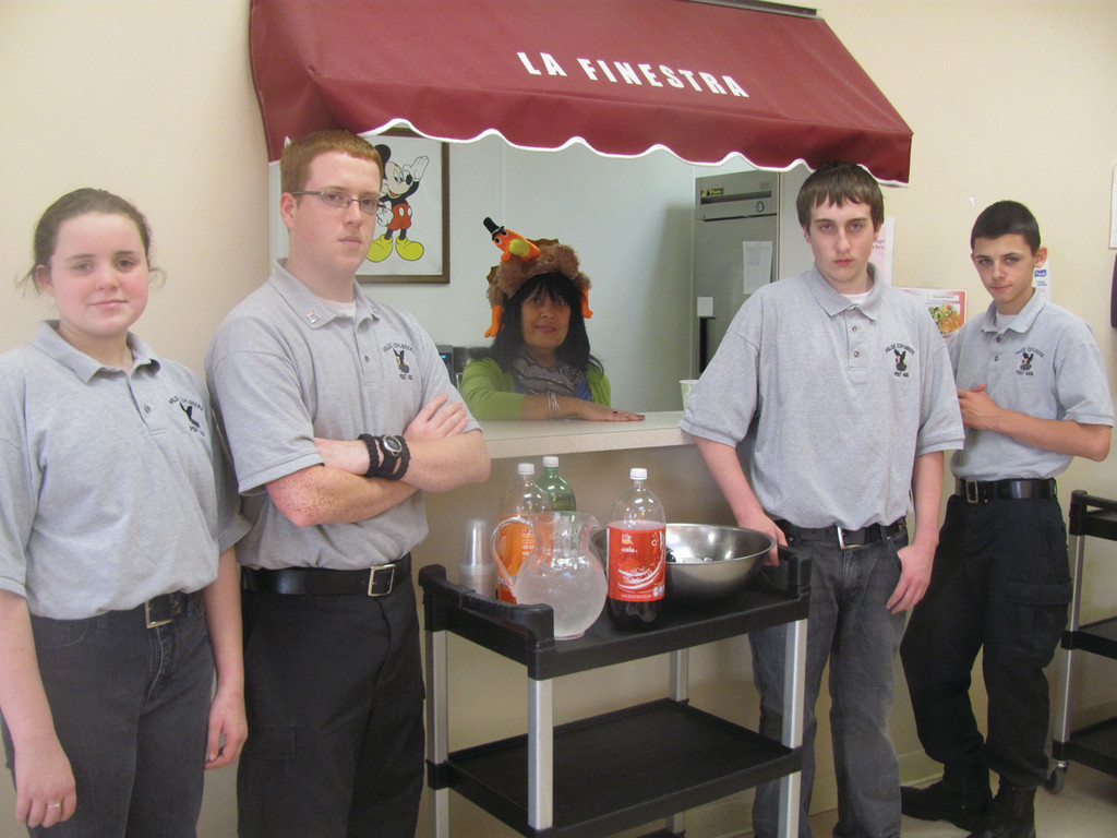 While Denise Bell manned the Johnston Senior Center kitchen window, members of the Johnston Police Explorers Post 405 volunteered their time to serve coffee and soft drinks to large crowd that attended the third annual Meat Raffle.
