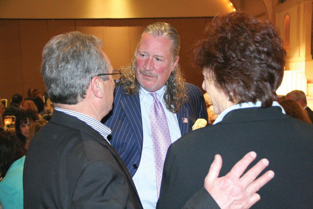FRIENDS IN THE CROWD: John Hazen White Jr. talks with Ron Caniglia and Candi Castaldi prior to the start of CCRI's Changing Lives celebration Thursday evening.