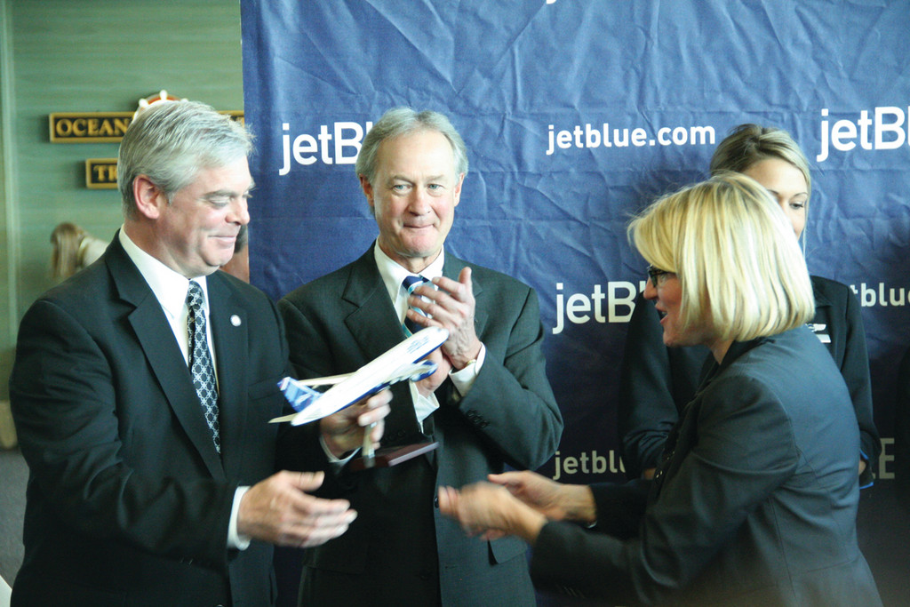 A PLANE FOR THE MAYOR: Joanna Geraghty, jetBlue�s executive vice president and chief people officer, presented Mayor Scott Avedisian with a model of the airline�s planes. Governor Lincoln Chafee, who looks on, got one last summer when the announcement was made on the State House steps that the airline would start service to Rhode Island.