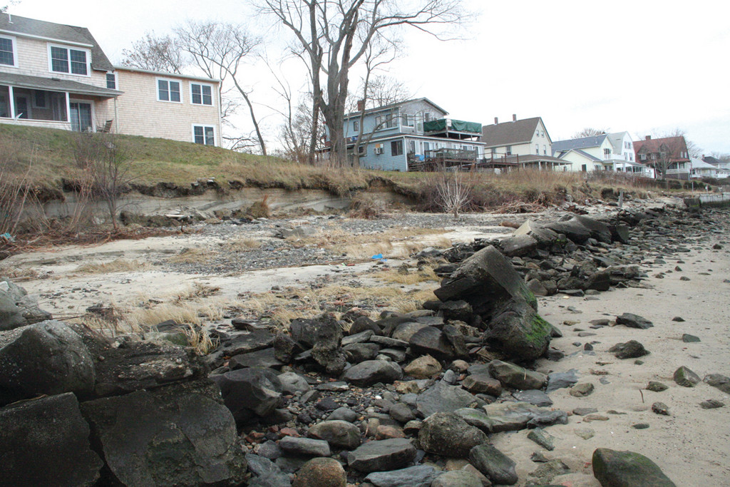 RETREATING SHORELINE: While not as vulnerable as the beach homes of southern Rhode Island, this section of Conimicut clearly shows the effects of past storms and Hurricane Sandy. The toppled seawall, the victim of the undermining of prior storms, lie on the sand with the headland they once held back freshly eroded by the surge and waves of Sandy. Those properties that still have walls or a groin of boulders were largely not impacted by the storm.