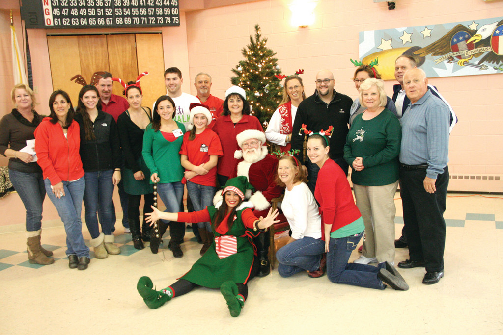 BE OF GOOD CHEER: Chamber employees and volunteers and Beacon staff members gather for a group shot with Santa following Saturday's breakfast and photo shoot with Santa.