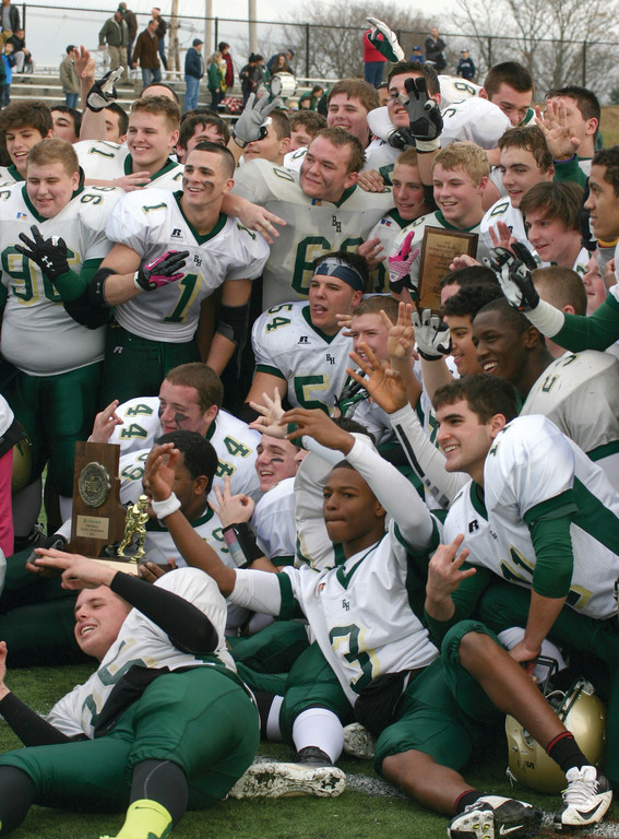 FAMILIAR MOMENT: Hendricken players pose for photos after receiving the state championship trophy for the third year in a row.
