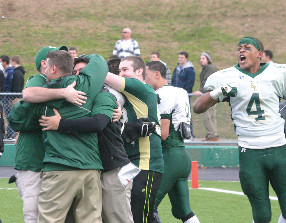 BIG MOMENT: Hendricken coaches share an embrace while senior Romario Rousseau celebrates.