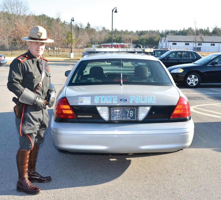 TAKE CARE: Colonel Steven O'Donell of the Rhode Island State Police is pictured with a State Police vehicle as he helped kick of the KDMF magnet campaign by putting magnets on 100 cruisers throughout the state. Businesses have also joined in the campaign to help raise awareness of drunk and distracted driving.