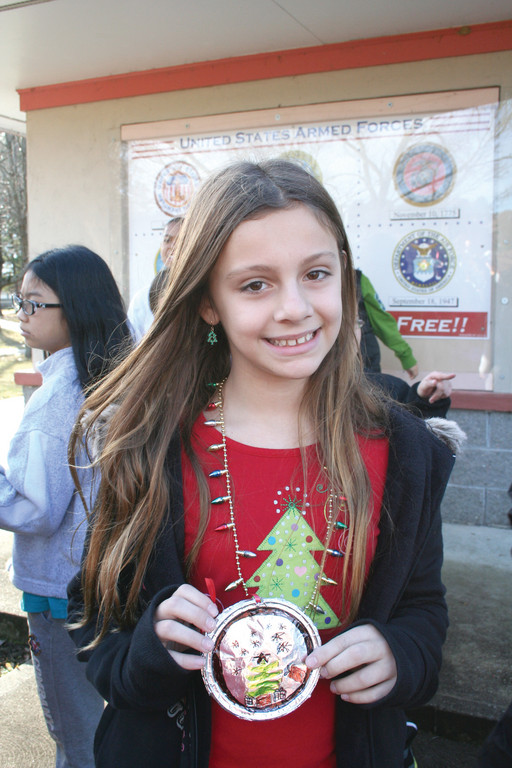 Fifth grader Megan Ranucci shows off the ornament she made to decorate Winsor Hill's tree.