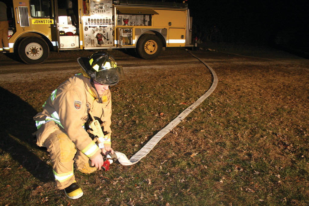 A Johnston Fire recruit prepares the fire hose before going into the burn trailer at the East Greenwich Fire Department.