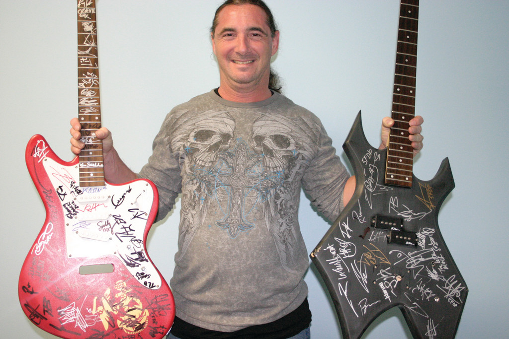 ROCKIN� AND ROLLIN� IN TOYS: Local musicians and music lovers are uniting for two events to collect toys and funds for Toys for Tots. Cranston resident Eric Tier (above) holds two autographed instruments that are up for bid, while father-son duo Jack and Jesse Gauthier are doing a small tour to support the cause.