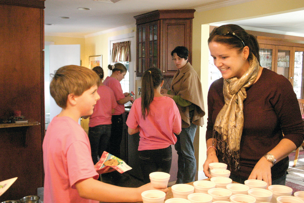 HOT CHOCOLATE, WARM HEARTS: Julie passes out hot chocolate to fifth grader Daniel Nygren, 10. Daniel and the other children said they felt happy, excited and awesome to sing at Walker's home. Many of them had her as a first grade teacher at Greenwood, where she taught for 23 years. Previously, she taught at St. Rose of Lima School for three years and St. Matthew School in Cranston for one year