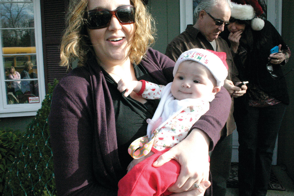 FIRST CHRISTMAS: Sarah holds her 4-month-old daughter, Drew, during the festivities. This will be the baby's first Christmas, as her age and hat indicate.