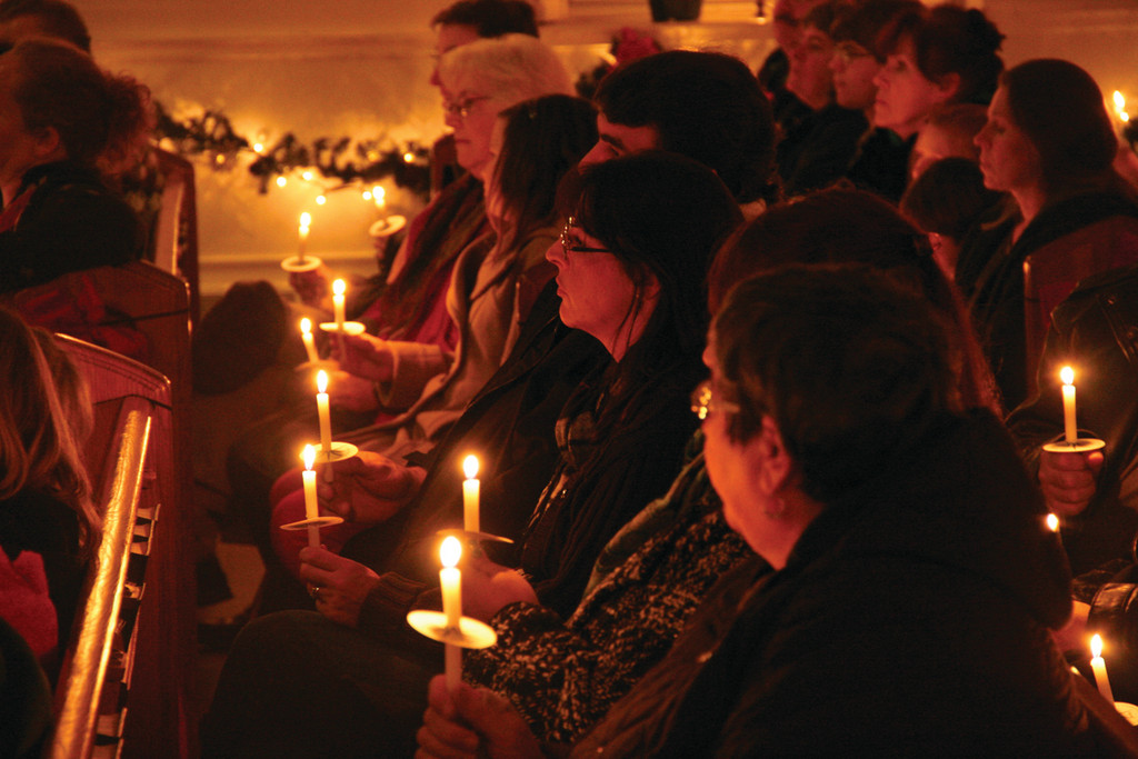 The Conimicut Village Association annual Christmas tree lighting Friday at the village center was followed by a community gathering in the Woodbury Union Church where residents were treated to a medley of seasonal songs by the Aldrich Junior High School select chorus under the direction of Sandra Brown. Church lights were turned down and candlelight set the tone.