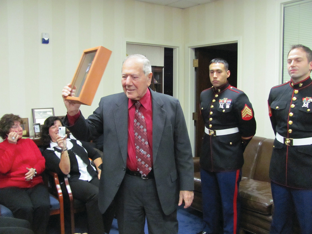 GETTING WHAT IS OWED TO HIM: Cranston native Mario Perri, 90, holds up his encased World War II medals he received at a ceremony hosted by United States Senator Sheldon Whitehouse in Providence.