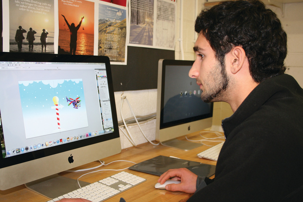 "IN CHARGE OF GRAPHICS: Mike Pescione, a junior in the CACTC Graphic Communications program, works on the design for ""Choppy,"" the helicopter featured in the activity books being created by the students in the program. The book will accompany the helicopters."