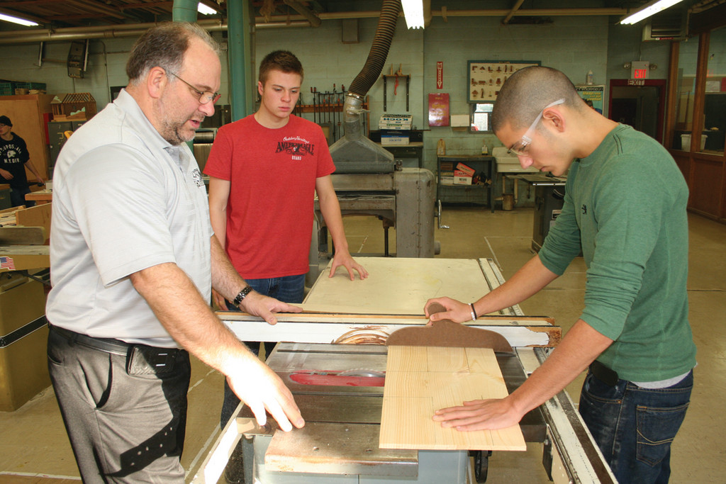 OVERSEEING THE ELVES: Craig Sacco works with Nick Krupa on this year's project as Tom Paliotte looks on.