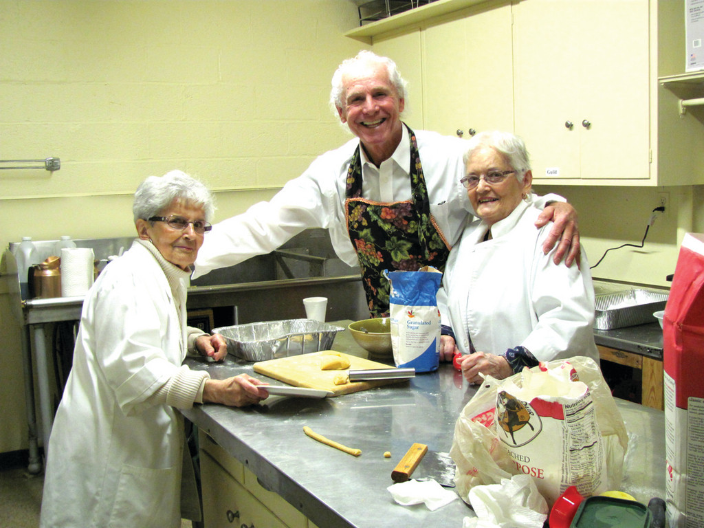 Volunteer chefs take a break from baking duties last Thursday morning for a quick coffee. Pictured here, Bob Casey hugs Marie Krapf and Ann Dalo before getting back to rolling and cutting the dough.
