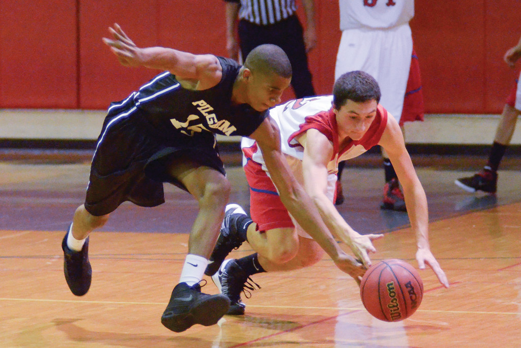 LOOSE BALL: Pilgrim's Letrelle Johnson (left) and Toll Gate's Ben Mann chase after the ball in Friday's rivalry game.