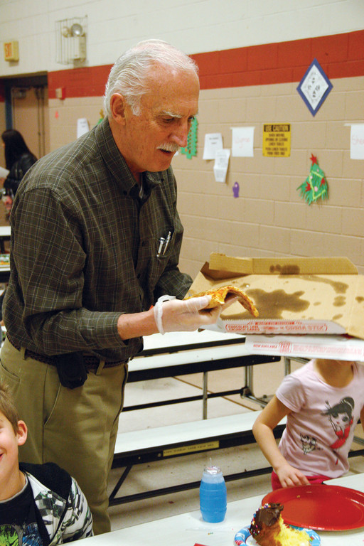 PIZZA FOR EVERYONE: Rotary member Paul Mellin passes out pizza for the girls and boys.