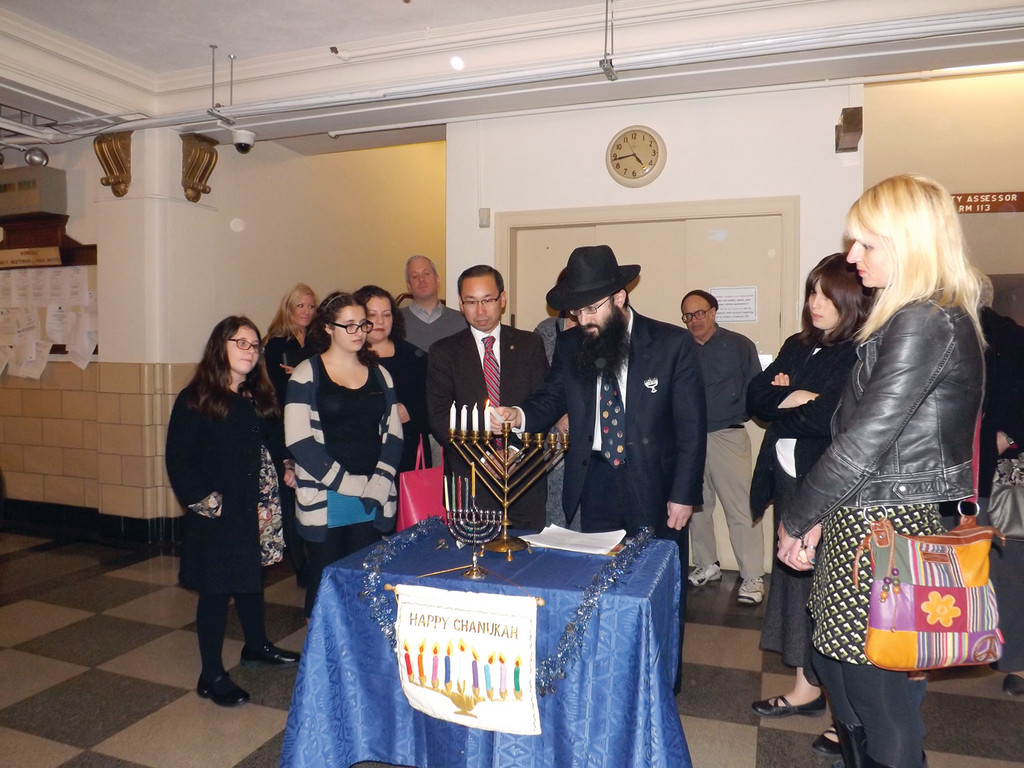 THE FOURTH CANDLE IS THE LIGHT OF FAMILY: Cranston residents and Mayor Allan Fung gather around the menorah as Rabbi Yossi Laufer lights the candles and says the blessings.