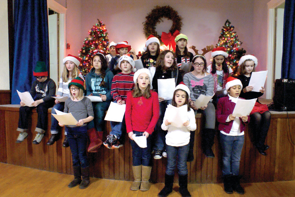 WITH SONG: Members of the BASICS choir sing Christmas Carols inside the Oaklawn Grange after the Christmas Tree and Gazebo were lit.