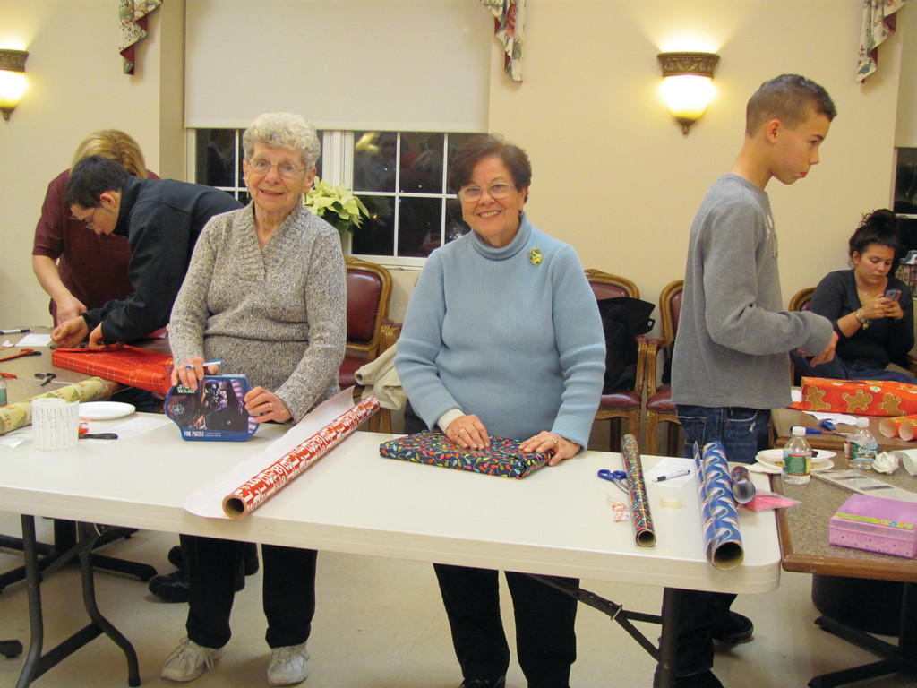 Claire Mathieu and Adeline Zany, who are volunteers at the Johnston Senior Center, wanted to help the Explorers Post 405 wrap presents last Thursday evening.