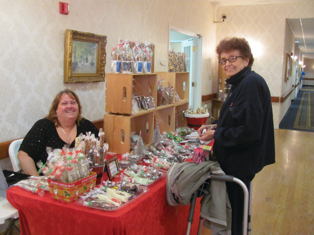 Esther Larson (right) a resident at The Bridge at Cherry Hill, purchases a Christmas gift from Jeanne Simonin Tuesday. Simonin, who owns Chocolates by Jeanne, was also on hand Tuesday to make a special donation to Tri-Town Community Action.