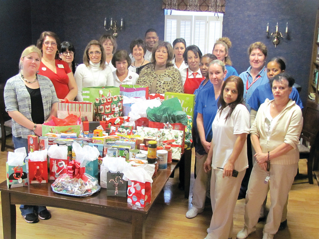 "These are just some of the many staff members at The Bridge at Cherry Hill who donated everything from clothes to toys that were presented to the Tri-Town Community Action Program Tuesday. The gifts, General Manager Maryann Grace said, ""will give a Johnston family of four a very nice Christmas."""