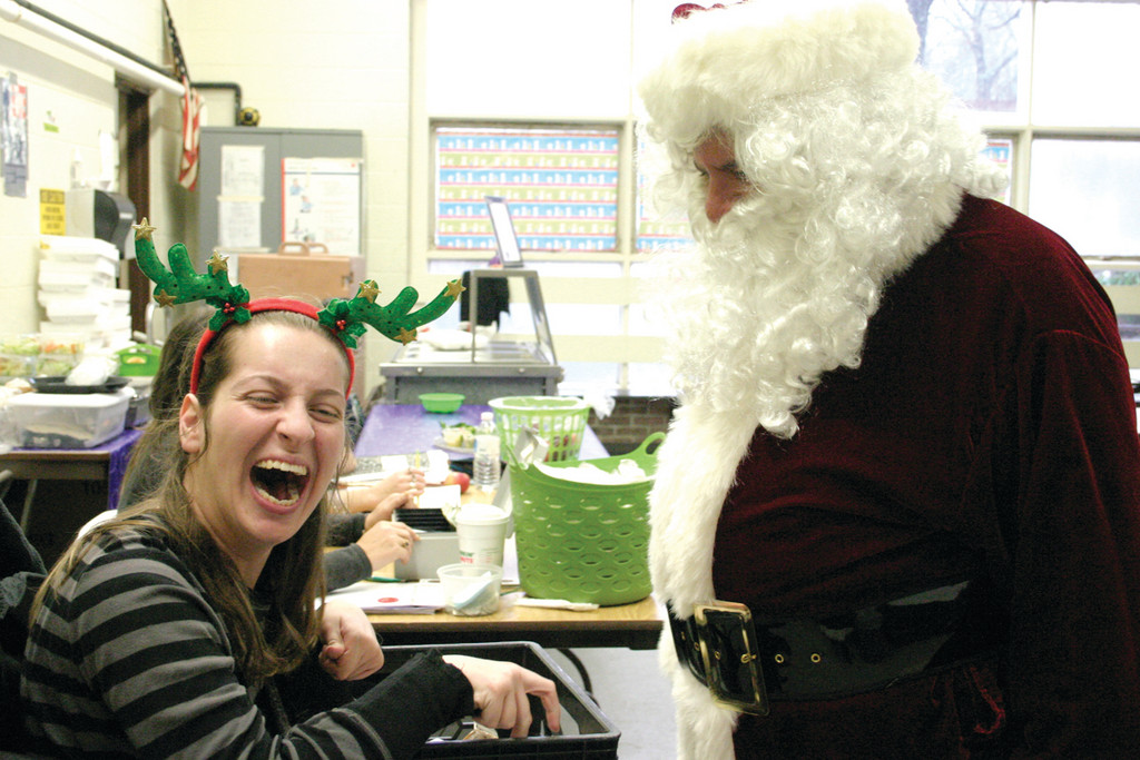 "REINDEER GAMES: Katie McAuslin, a 2010 Toll Gate graduate and a 2004 John Wickes graduate, volunteers at the school three or four times a week. She got a kick out of chatting with Santa, and said she enjoys helping the school. ""I like the kids,"" she said."