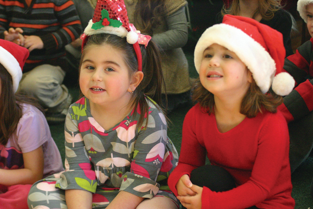 Emma Ierfino and Ava Vendituoli sit and listen carefully to a story after telling Santa what they want for Christmas.