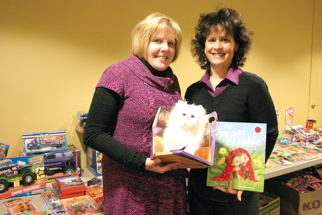 A TIME OF GIVING: Norwood branch Boys & Girls Club Executive Director Lara D'Antuono and Associate Executive Director Karin Kavanagh are pleased they were able to help Club parents, as they set up a Christmas store.