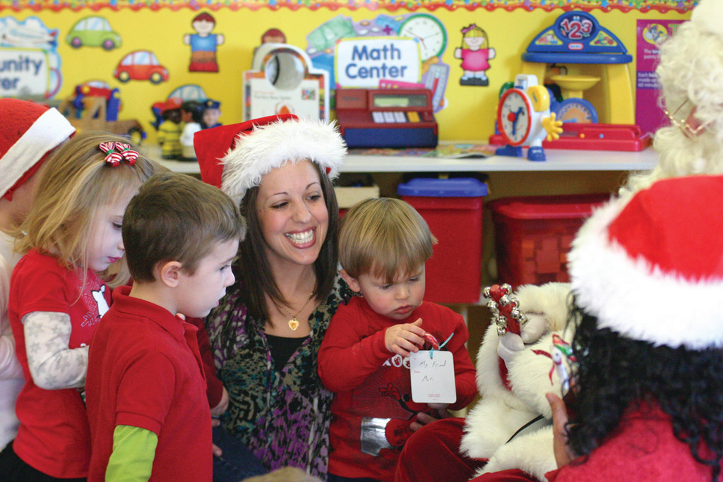 Head teacher Michelle Avella introduces the children to Santa. On her lap is Shane Branch.