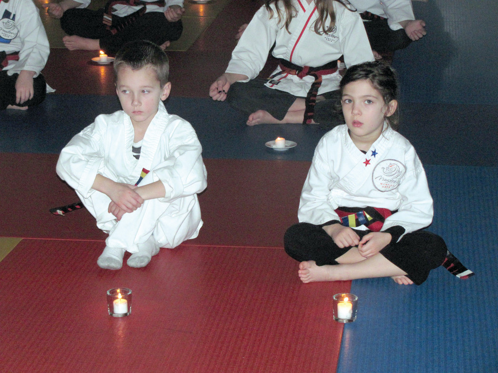Thirty-three children at Mastery Martial Arts sit patiently and await receipt of their black belt.