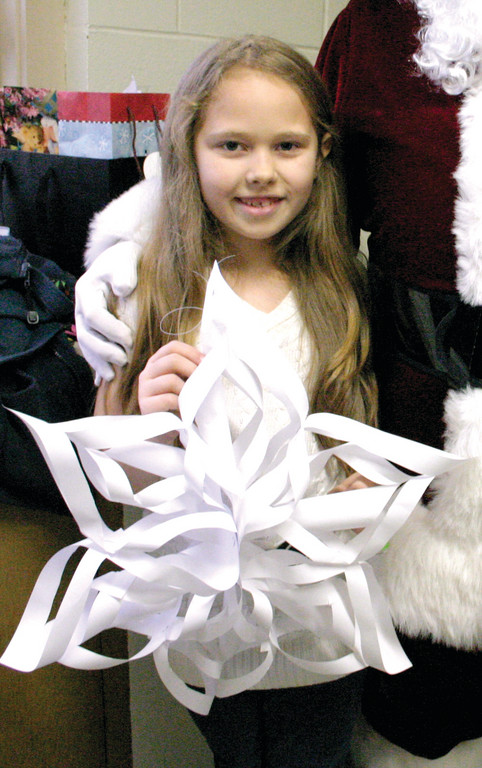 "CRAFTED FROM THE HEART: Natalia DeCosta, 8, a third grader, holds up a paper snowflake she made for Sandy Hook students and their families. While Natalia and the rest of the third graders made snowflakes, other grades also made crafts for the cause. Also, Governor Lincoln Chafee declared Dec. 21 a Rhode Island day of mourning, and a moment of silence was held at 9:30 a.m. to honor the victims of the Dec. 14 shooting. Any buildings with bells were asked to ring them 26 times during the moment of silence to honor each life that was taken at Sandy Hook. On a lighter note, Natalia shared her Christmas sentiments. ""It's not about the presents,"" she said. ""We like celebrating Jesus' birthday."""
