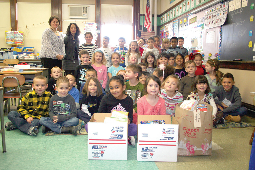A LESSON IN GIVING: Sarah Perra and Lisa Colantonio pose with their first graders at Waterman and just a few of the items they collected before the winter vacation began. They sent out five boxes first, with four more still to go.