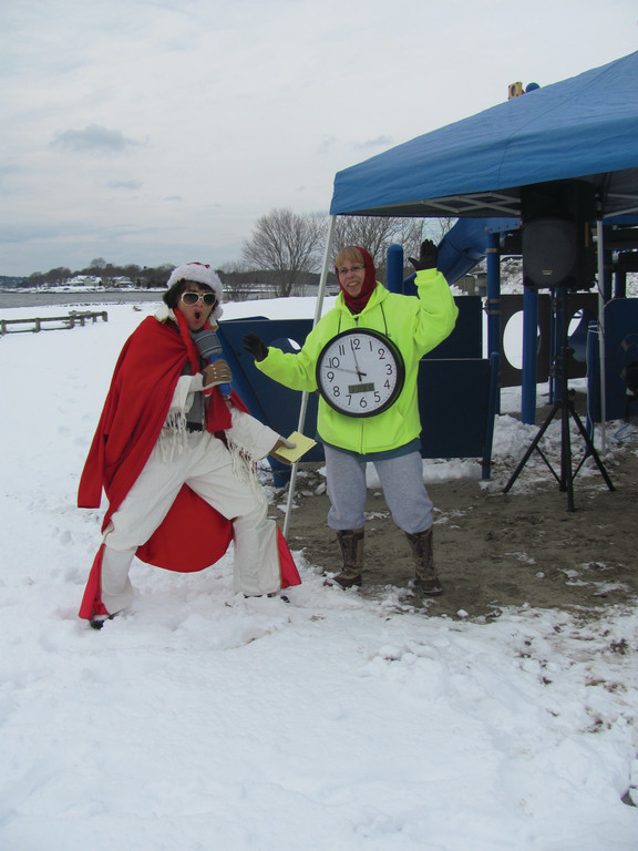 "SEAWALL SIDEKICKS: Amy ""Elvis"" Beth (left) of Cranston provided some entertainment prior to Monday's Seawall Splash at Oakland Beach. The countdown was kept by Priscilla Ingram, who carried an oversized clock leading to the annual plunge into Greenwich Bay."